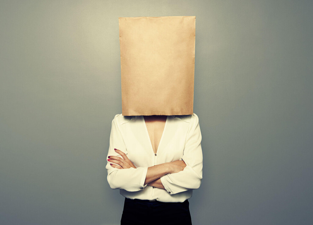 28422335 - businesswoman hiding under empty paper bag over dark background